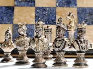 silver chess set in front of a blue and cream stone board