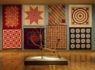 a gallery with eight quilts on the wall and a spinning wheel