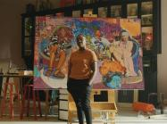 Artist Amani Lewis stands in front of work in promo video for google partnership to promo black-owned businesses