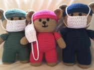three crocheted teddy bears in scrubs and face masks