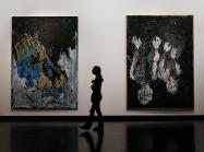 a silhouetted figure walks between two large abstract paintings