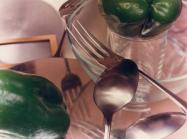 Jan Groover photograph of spoons, forks and green bell peppers on a pink tablecloth with reflected light