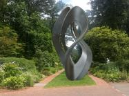 a photo of a large metal sculpture in a twisted organic form in a lush garden setting
