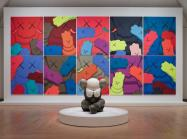 Installation view, KAWS: WHAT PARTY, Brooklyn Museum, February 26, 2021 - September 5, 2021. Features sculpture in front of a series of several flat images of