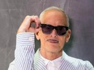 photograph of john waters, an older white man with a small moustache, wearing sunglasses and a seersucker suit