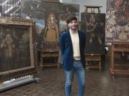 José Luis Lazarte Luna, Assistant Conservator in Paintings Conservation, who was born and raised in Lima, Peru, stands in front of several paintings in the Cuzco School style that were recently gifted to The Met