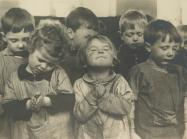 group of small children close their eyes in prayer