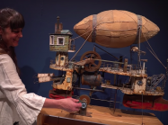 Woman turns handle of steampunk blimp ship sculpture
