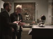 Adam Savage and Met Curator look at child's breastplate in glass case