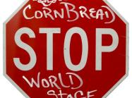 "Art by CornBread: Stop Sign with ""Cornbread"" sprayed above ""STOP"" and ""World Stage"" Below"