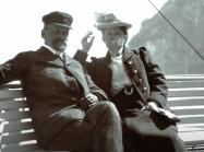 Photograph of Wilhelm and Henny Hansen smoking in front of water