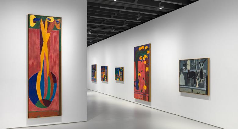 installation view, brightly colored tall paintings in a gallery with white walls