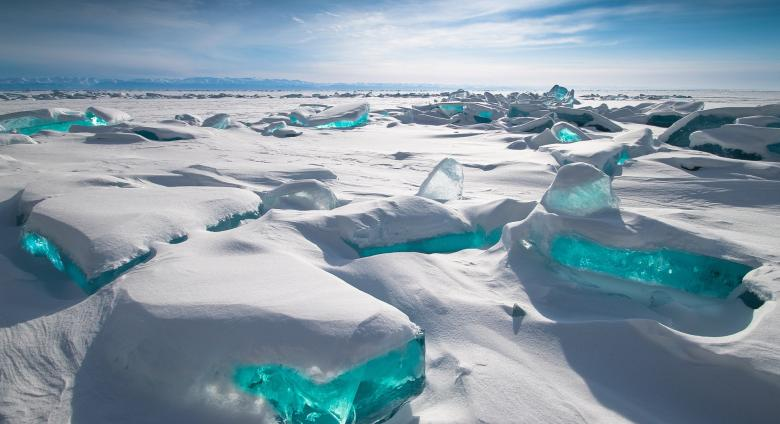 a snowy landscape with bit of brilliant blue ice