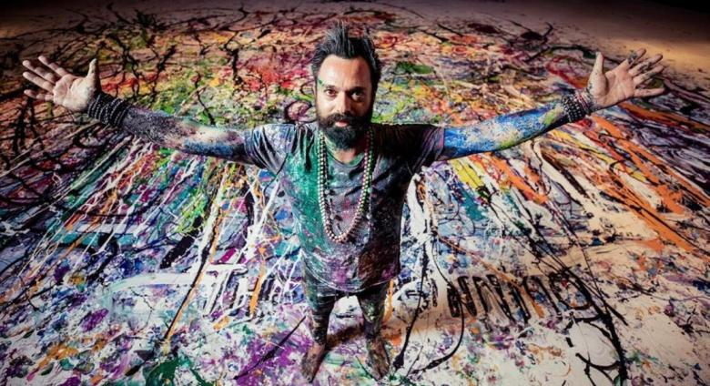 Artist Sacha Jafri covered in paint with arms spread, standing on a large paint-covered canvas