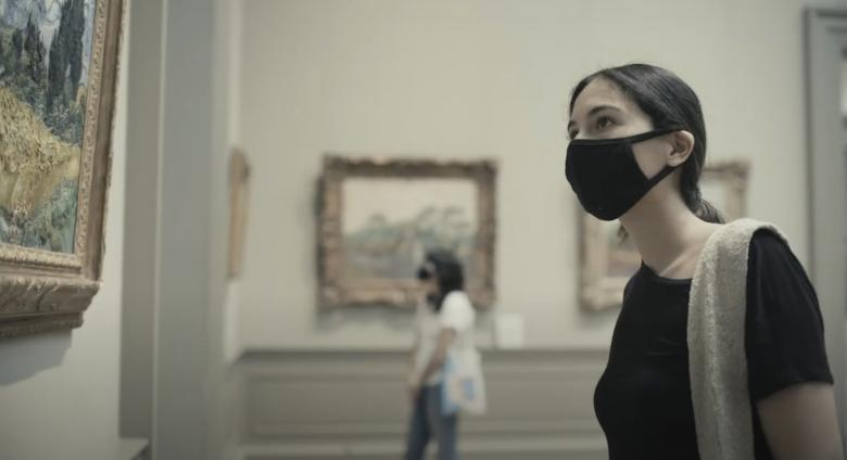 woman in mask looks at painting in the met