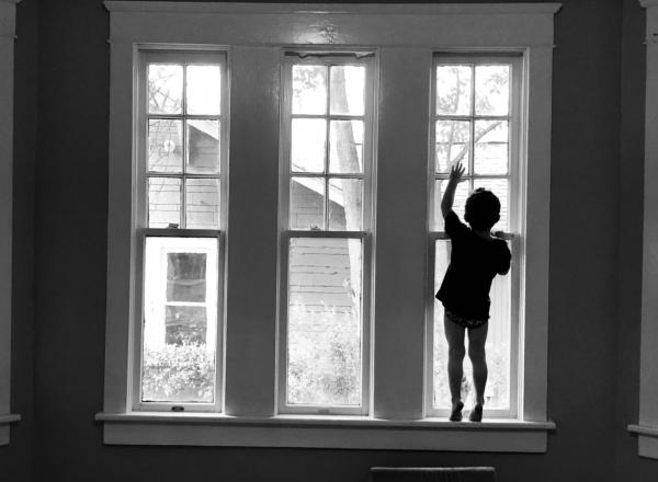 the silhouette of a child standing in a bay window