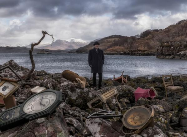 John Akomfrah, Video still from Vertigo Sea, 2015. A man in old timey garb stands on the shore of a pond littered with clocks.