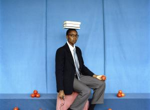 artist sits with books on head, surrounded by piles of tomatoes