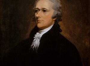 Alexander Hamilton Sits in a dark suit and looks off to the left.