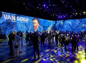 View of Exhibition Van Gogh: The Immersive Experience at AREA15. The room is filled with people in VR goggles, the lighting on the crowd has brought starry night into the room, details of stary night are projected on the walls.