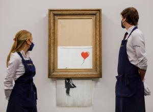Two Sotheby's employees stand, framing the Banksy piece on auction day Oct 14, 2021