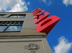 "the word ""design"" in large red letters running up the corner of a building towards a bright blue sky"
