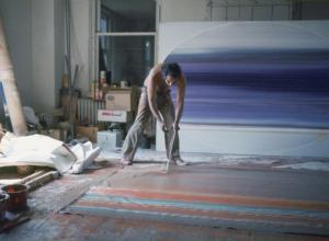 Ed Clark painting on the floor using a broom