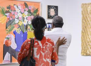 A couple at the Affordable Art Fair NYC, taking a photo of a bright, contemporary still life floral painting.