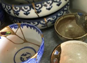 detail photo of a collection of pottery wares repaired via Kintsugi
