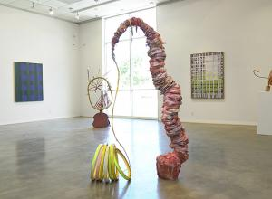 Installation view of Evenso: The Common & The Curious, showing sculpture in center of room and works on walls