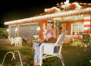 a woman in a pink bikini and sunglasses sits in a lawn chair in front of her home at night