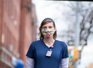 "Catherine ""Cat"" Carnes, a registered nurse, stands on the street wearing a mask and scrubs"