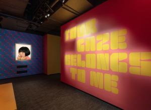 exhibition entry way with title on one wall and photo of the artist flipping the viewer off on the other wall. The image is closely cropped on her face.