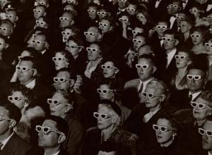 Audience watches movie wearing 3-D spectacles, 1952