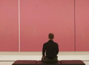 man sitting in front of pink canvas