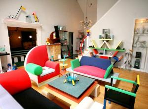 Living room installation filled with bright furniture made from odd shapes.