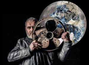 artist standing with metal fan in front of moon painting/ sculpture