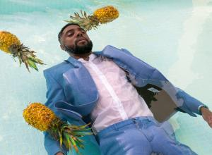 A man with dark skin, wearing a suit floats in a pool amongst three pineapples.