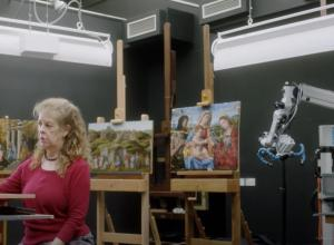 conservator looks at computer in front of several paintings