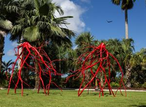 large red metal sculpture of roots in a garden