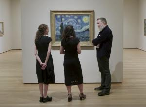 group looks at Starry Night on wall in gallery
