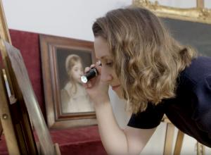expert examines painting with flashlight