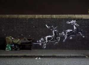 banksy mural of reindeer pulling a public bench