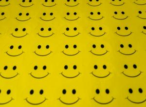 a sheet of yellow fabric with rows and rows of smiley faces