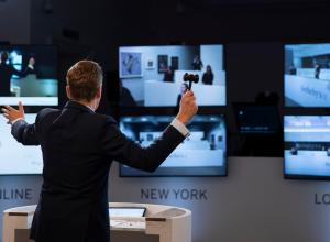 an auctioneer with a gavel stands in front of three large computer screens