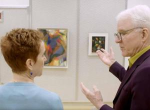 Steve Martin looks closely at work of art on wall