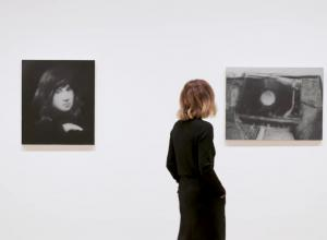 Curator walks through gallery of black and white images.