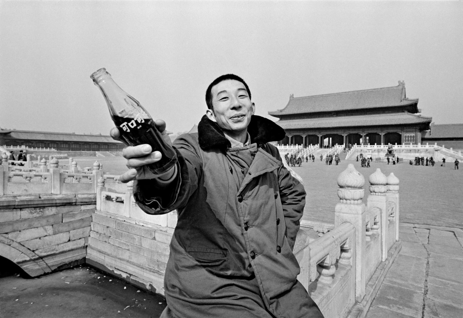 """Coca-Cola Feel the Taste!"" A young man proffers the iconic glass bottle which symbolizes Coca-Cola around the world. The Coca-Cola Company had just resumed production in China. Forbidden City, Beijing, 1981."