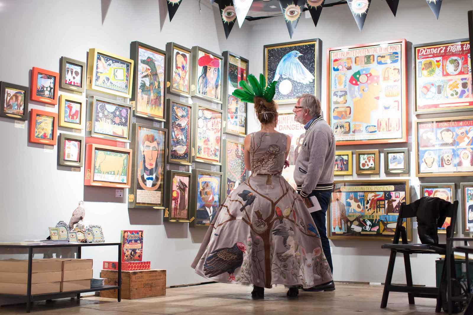 Man and woman look at art on wall at fair 2018
