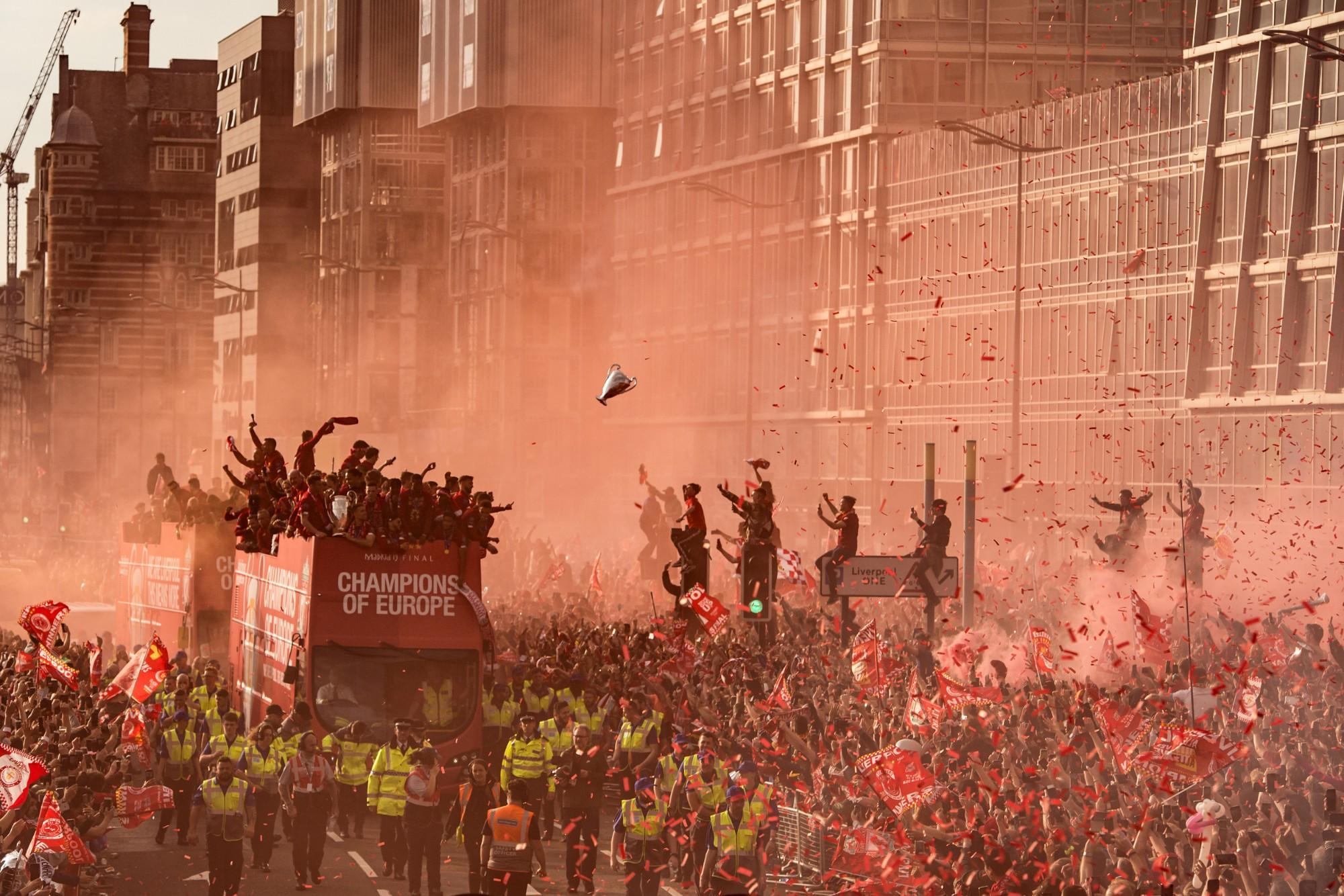 A trophy-shaped balloon floats over the crowd in Liverpool, England, as football fans line the streets on 2 June during the open-top bus parade celebrating Liverpool's win against Tottenham Hotspur in the UEFA Champions League final.